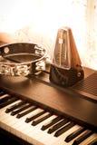 在一架钢琴的节拍器与小手鼓 免版税库存图片