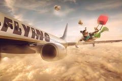 在一架移动的飞机的翼的妇女飞行,在与把手的云彩 免版税图库摄影