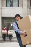 在一栋宿舍外面的家庭移动的箱子在学院,儿子微笑 库存照片