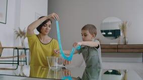 在一栋白色公寓坐地板妈妈和男孩过去常常播放一个伸缩自在的彩色塑泥玩具,笑和微笑 影视素材