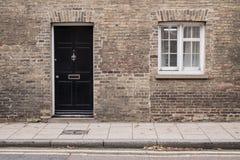 在一栋维多利亚女王时代的房子居民住房的一个被恢复的砖墙上的黑前门 免版税库存图片