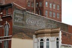 在一栋老砖瓦房的葡萄酒手画可口可乐标志 免版税库存图片