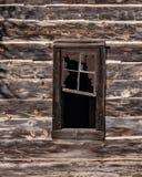 在一栋被放弃的手制的原木小屋的窗口在Mosier,俄勒冈附近 库存照片
