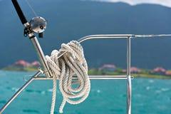 在一根保险索和一根钓鱼竿附近被栓的绳索在游艇 免版税图库摄影