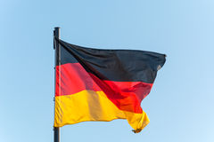 在一根杆的德国旗子与蓝天 免版税库存照片