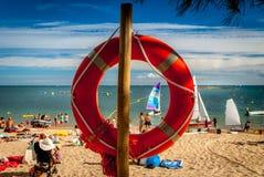 在一根杆的救生圈在一个沙滩用蓝色海洋水 库存图片