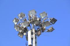 在一根杆的许多明亮的聚光灯反对蓝天 免版税库存照片