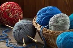 在一根柳条筐和编织针的多彩多姿的毛线 图库摄影