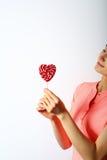 在一根棍子的红色心脏糖果在一个少妇的手上 免版税库存图片