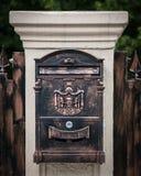 在一根白色柱子的古铜色邮箱由石头制成 图库摄影
