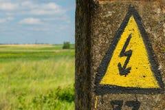 在一根老电柱子的普通高压危险标志 叫喊 库存照片