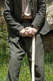 在一根走的藤茎棍子的年长人倾斜 库存图片