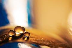 水滴在一根金黄羽毛的有蓝色背景 与水滴的一根羽毛  选择聚焦 免版税图库摄影