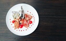 在一根骨头的烤牛排用在一块白色板材的蕃茄 断送热肉 顶视图 免版税库存图片
