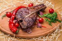 在一根骨头的开胃牛排,用蕃茄,胡椒,在一个木板 水平的框架 库存照片