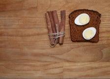 在一根黑面包和肉桂条的鹌鹑蛋在broun木桌上 免版税库存照片
