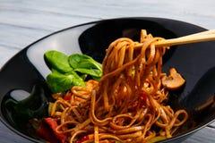 在一棵圆的板材、米线、圆白菜嫩卷心菜和油煎的菜的繁体中文盘 库存图片