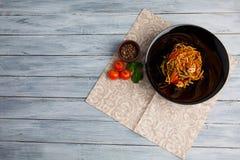 在一棵圆的板材、米线、圆白菜嫩卷心菜和油煎的菜,红色西红柿的繁体中文盘 免版税库存图片