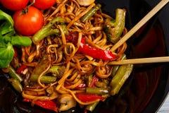 在一棵圆的板材、米线、圆白菜嫩卷心菜和油煎的菜,红色西红柿的繁体中文盘 免版税库存照片