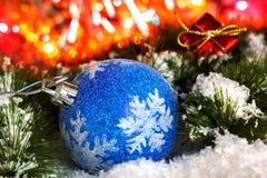 在一棵圣诞树的多雪的分支的球反对发光的闪亮金属片背景的  发光的光 库存照片