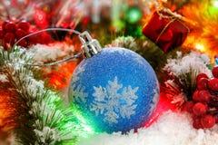 在一棵圣诞树的多雪的分支的球反对发光的闪亮金属片背景的  发光的光 免版税图库摄影