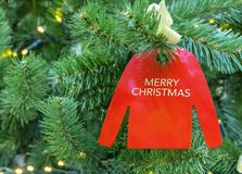 在一棵圣诞树的装饰品以与题字圣诞快乐的一件红色套头衫的形式 图库摄影