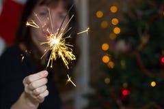 在一棵圣诞树附近的女孩与闪烁发光物 库存图片
