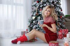 在一棵圣诞树附近的美丽的妇女与一杯咖啡用蛋白软糖 免版税库存图片