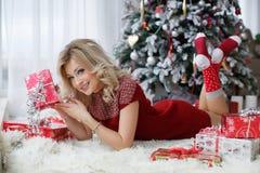 在一棵圣诞树附近的美丽的妇女与一杯咖啡用蛋白软糖 库存照片