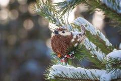 在一棵多雪的树的分支的圣诞节葡萄酒手工制造玩具鸟 免版税库存图片