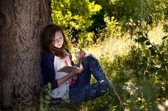 在一棵大树旁边的女孩读书 免版税库存照片