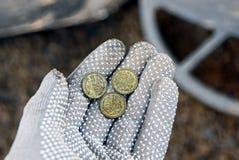 在一棵开放棕榈的三枚小银币在一副灰色手套 免版税库存照片