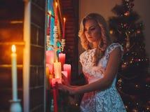 在一棵新年树附近的妇女与礼物和蜡烛 库存图片