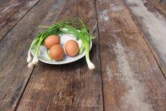 在一棵板材和葱的新鲜的鸡鸡蛋在木桌里 库存图片