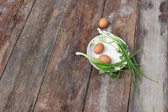 在一棵板材和葱的新鲜的鸡鸡蛋在木桌里 免版税库存图片