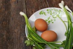 在一棵板材和葱的新鲜的鸡鸡蛋在木桌里 库存照片