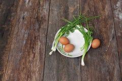 在一棵板材和葱的新鲜的鸡鸡蛋在木桌里 图库摄影