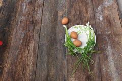 在一棵板材和葱的新鲜的鸡鸡蛋在木桌里 免版税库存照片