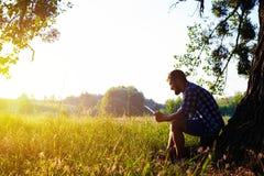 在一棵树下的年轻人在日落背景在领域的 免版税库存图片