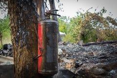 在一棵树的灭火器在被烧的房子旁边 库存照片