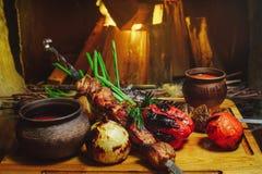 在一棵树的烤肉和菜葱蕃茄和胡椒精妙的屑子用调味汁和新鲜蔬菜,舒适餐馆 库存照片