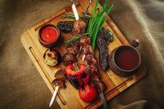 在一棵树的烤肉和菜葱蕃茄和胡椒精妙的服务用调味汁和新鲜蔬菜,舒适restauran 免版税图库摄影