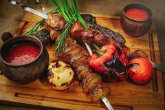 在一棵树的烤肉和菜葱蕃茄和胡椒精妙的服务用调味汁和新鲜蔬菜,舒适restauran 图库摄影