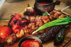 在一棵树的烤肉和菜葱蕃茄和胡椒精妙的服务用调味汁和新鲜蔬菜,舒适restauran 库存照片