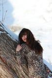 在一棵树附近的体贴的女孩在冬天 免版税库存照片
