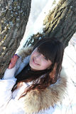 在一棵树附近的愉快的女孩在冬天森林里 库存图片