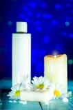 在一棵白色瓶、肥皂、蜡烛和春黄菊的身体化妆水开花 图库摄影