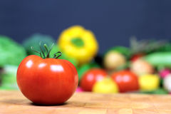 在一棵砧板和各种各样的菜的新鲜的蕃茄 免版税库存照片
