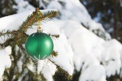 在一棵积雪的冷杉分支的圣诞节玩具 免版税库存照片