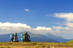 在一棵草的两个远足者背包与山峰视线内 汽车 免版税图库摄影